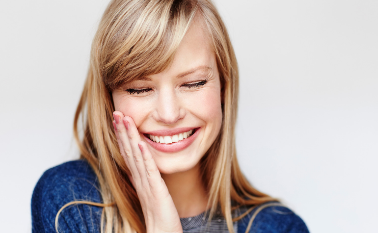 a blonde lady smiling and touching her cheek after receiving winter skincare treatments